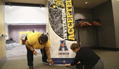 Carmen Hytche, director of special events and Sandra Denneler adjust a sign before an official announcement at Wichita State University in Wichita, Kan., Friday, April 7, 2017. Wichita State accepted an invitation Friday to join the American Athletic Conference, ending a relationship with the Missouri Valley Conference that dated back 72 years. (Bo Rader/The Wichita Eagle via AP)