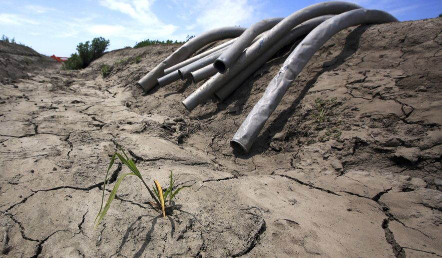 FILE - This May 18, 2015 file photo shows irrigation pipes along a dry irrigation canal on a field near Stockton, Calif. On Friday, April 7, 2017, California Gov. Jerry Brown declared an end to the state's water emergency following a five-year drought that reduced rivers to trickles, farmland to dust fields and forests to swathes of dead trees. The state's $47 billion farming industry took a hit as government-supplied irrigation supplies were drastically reduced. Farmers dug more wells, sucking up groundwater in the Central Valley and causing the ground to sink. (AP Photo/Rich Pedroncelli, File)