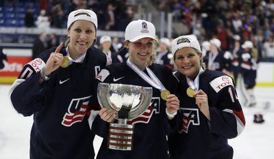 U.S. forward Meghan Duggan, left, defender Monique Lamoureux, center, and forward Brianna Decker pose with the winner's trophy after the team defeated Canada 3-2 in overtime in the women's world hockey championships, Friday, April 7, 2017, in Plymouth, Mich. (AP Photo/Carlos Osorio)