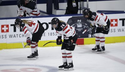 Canada forwards Sarah Potomak (44), Natalie Spooner (24) and Brianne Jenner (19) skate back to the bench after overtime against the United States in the gold-medal game of the women's world hockey championships, Friday, April 7, 2017, in Plymouth, Mich. (AP Photo/Carlos Osorio)