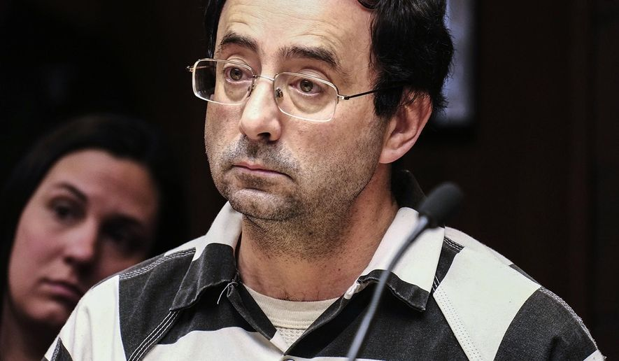 FILE - In this Feb. 17, 2017, file photo, Dr. Larry Nassar listens to testimony of a witness during a preliminary hearing, in Lansing, Mich. Nassar, a Michigan sports doctor accused of sexually assaulting dozens of women and girls, had his medical license revoked by Michigan regulators Thursday, April 6, 2017, for at least three years. (Robert Killips /Lansing State Journal via AP, File)
