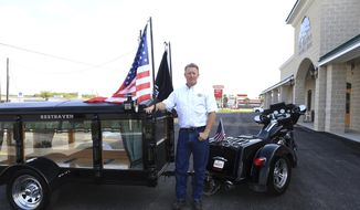Lee Hickel, owner of Resthaven Funeral Home, stands with his motorcycle hearse in Aransas Pass, Texas on March 27, 2017.  Hickel purchased the hearse about five years ago and found the Harley-Davidson trike bike to pull it in Mississippi.  (Rachel Denny Clow/Corpus Christi Caller-Times via AP)