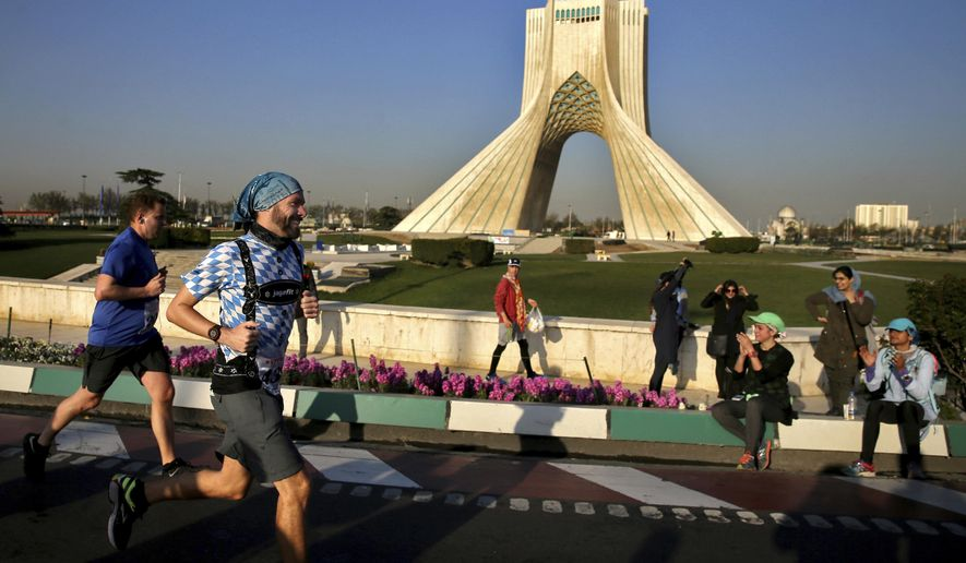 "Participants of the Tehran Marathon runs while women clap in front of the Azadi (Freedom) monument tower in Tehran, Iran, Friday, April, 7, 2017. Iran's Track and Field Federation chief Majid Keyhani had said Wednesday there was no ban on any nationality in what he called the ""Persian Run."" (AP Photo/Ebrahim Noroozi)"