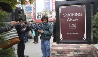 People gather at the smoking area in Tokyo, Friday, April 7, 2017. The senior World Health Organization official says Japan should go fully smoke-free in public places if it wants success in Tokyo Olympics and tourism promotion. (AP Photo/Koji Sasahara) ** FILE **