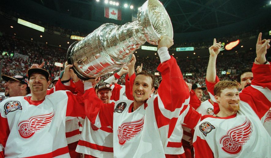 FILE - In this June 7, 1997, file photo, Detroit Red Wings' Tim Taylor, from left, Steve Yzerman and Doug Brown celebrate with the Stanley Cup after beating the Philadelphia Flyers 2-1 at Joe Louis Arena in Detroit. Detroit swept the best-of-7 Stanley Cup final series against the Flyers, giving the franchise its first championship since 1955. The arena will be the home of the Red Wings one more time on Sunday, April 9, 2017, when they host the New Jersey Devils. (AP Photo/Tom Pidgeon, File)