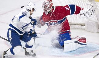 Montreal Canadiens goalie Carey Price (31) makes a save off Tampa Bay Lightning's Yanni Gourde during first-period NHL hockey action in Montreal,Friday, April 7, 2017. (Paul Chiasson/The Canadian Press via AP)