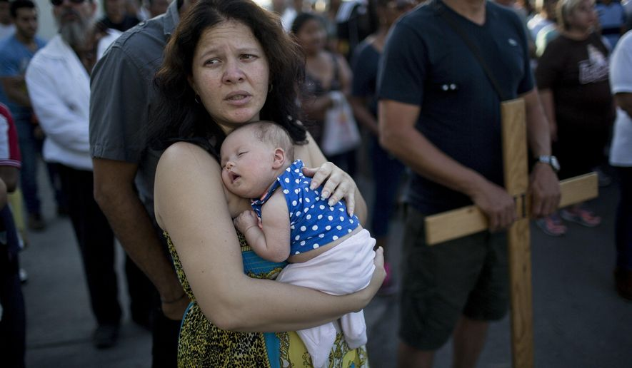 In this Friday, March 24, 2017 photo, Cuban Elaide Vilchez carries her one-month-old daughter Emily Melania Garcia during a religious procession adapted to reflect the plight of immigrants, in Nuevo Laredo, Mexico, across the border from Laredo, Texas. (AP Photo/Rodrigo Abd)