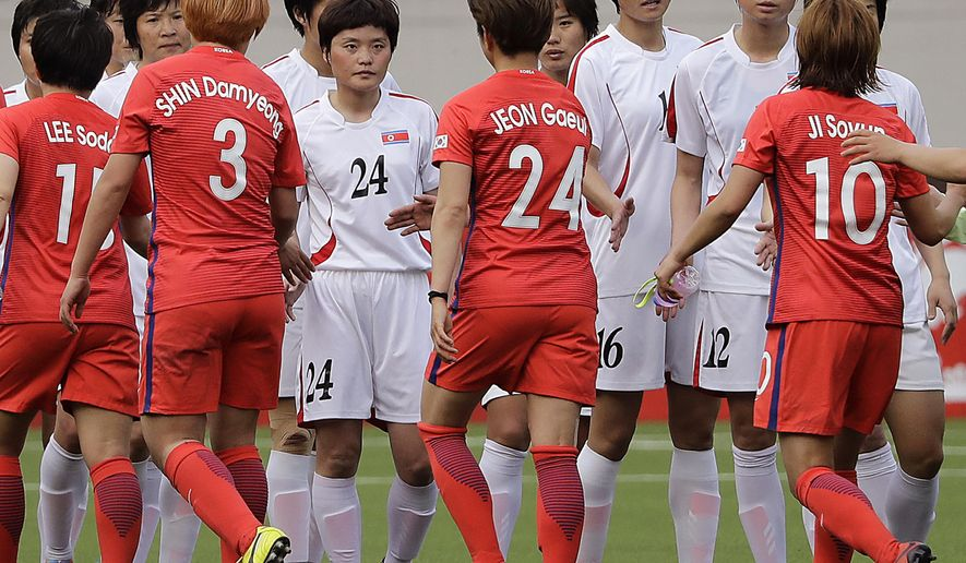 South Korean, in red uniforms, and North Korean women soccer players hi-five after their AFC Women's Asian Cup Jordan 2018 qualifying soccer match at the Kim Il Sung Stadium on Friday, April 7, 2017, in Pyongyang, North Korea. South Korea equalized the score to 1-1 at the end of the match. (AP Photo/Jon Chol Jin)