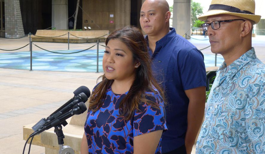 Chelsea Valiente, left, talks to reporters along with her husband Rey Valiente, center, and state Sen. Will Espero, right, at the Hawaii State Capitol on Friday, April 7, 2017, in Honolulu. The Valientes' son was seriously injured while attending a home day care and they are asking state Attorney General Doug Chin to investigate the case.  (AP Photo/Cathy Bussewitz)