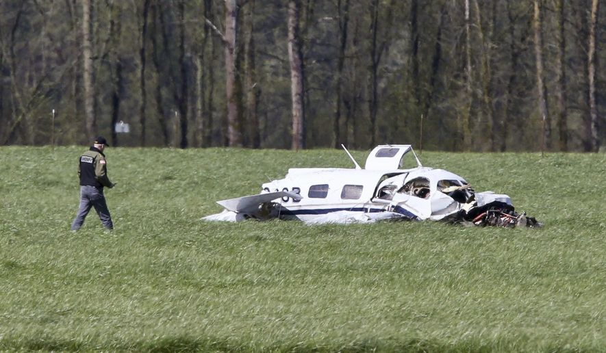 A Linn County Sheriff deputy approaches the scene of a small plane crash north of Harrisburg, Ore., that left four people dead, Friday April 7, 2017. (Collin Andrew/The Register-Guard via AP)
