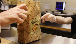 In this March 8, 2010, file photo, an employee passes an order to a customer at a Panera Bread store in Brookline, Mass. (AP Photo/Charles Krupa, File)