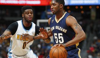 New Orleans Pelicans guard E'Twaun Moore, right, drives past Denver Nuggets guard Emmanuel Mudiay during the first half of an NBA basketball game Friday, April 7, 2017, in Denver. (AP Photo/David Zalubowski)