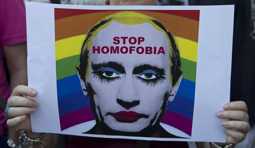 A woman holds a poster depicting Russian President Vladimir Putin during a protest in front of the Russian embassy in Madrid, Spain, on Aug. 23, 2013. (Associated Press/Paul White)