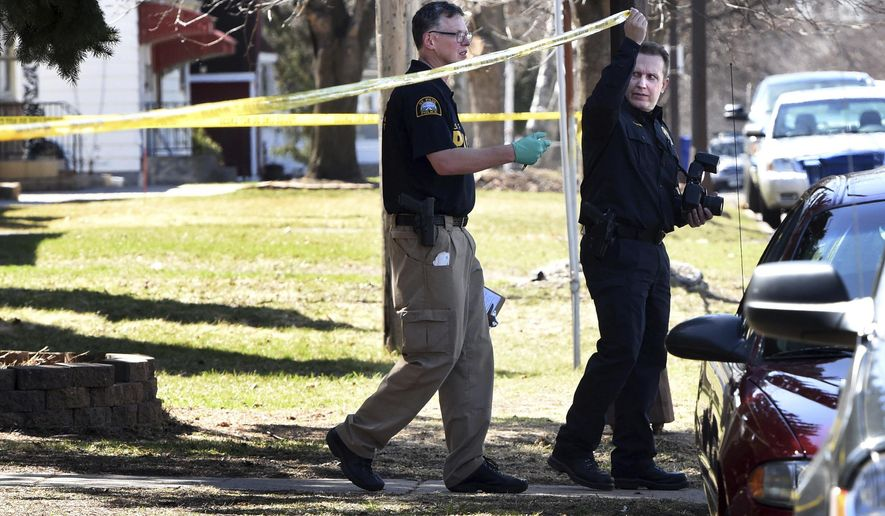 Investigators walk under police tape at the scene of an early morning shooting Friday, April 7, 2017, in St. Paul, Minn. Police say a suspect has been found dead after three people were fatally shot and a fourth person was critically injured in the shooting at an apartment building in St. Paul.  (Jean Pieri/Pioneer Press via AP)