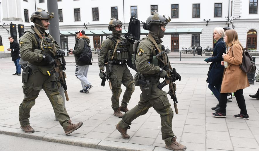"Armed police patrol outside the central station in Stockholm  after a truck crashed into a department store injuring several people in a different part of Stockholm, Sweden, Friday April 7, 2017. Swedish Prime Minister Stefan Lofven says everything indicates a truck that has crashed into a major department store in downtown Stockholm is ""a terror attack."" (Jessica Gow/ TT News Agency via AP)"
