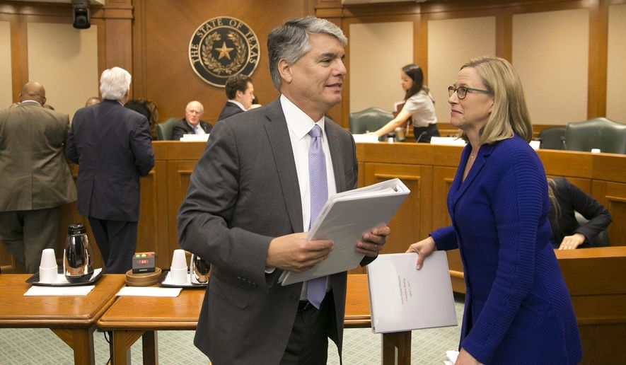 In this April 5, 2017, photo, University of Texas at Austin President Gregory Fenves, left, and Maurie McInnis, UT Executive Vice President and Provost, get up from their chairs at the Capitol after testifying on Senate Bill 2119 in Austin, Texas. (Jay Janner/Austin American-Statesman via AP)