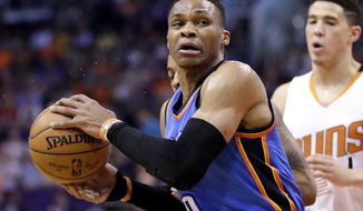 Oklahoma City Thunder guard Russell Westbrook (0) spins around Phoenix Suns guard Devin Booker during the first half of an NBA basketball game, Friday, April 7, 2017, in Phoenix. (AP Photo/Matt York)