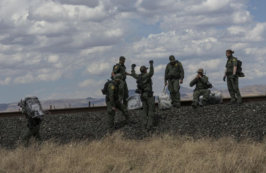 """U.S. Border Patrol agents carry bales of marijuana they found along the highway near Ryan, Texas, about 20 miles from the U.S.-Mexico border on March 28, 2017. One agent said, """"They (the smugglers) just leave it and come back another day. It's going to be sad when they come back for it."""" Drug interdiction is a core mission for the Border Patrol. (Associated Press) **FILE**"""