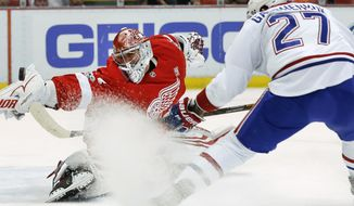 Detroit Red Wings goalie Petr Mrazek, left, stops a Montreal Canadiens center Alex Galchenyuk (27) shot in the first period of an NHL hockey game Saturday, April 8, 2017, in Detroit. (AP Photo/Paul Sancya)