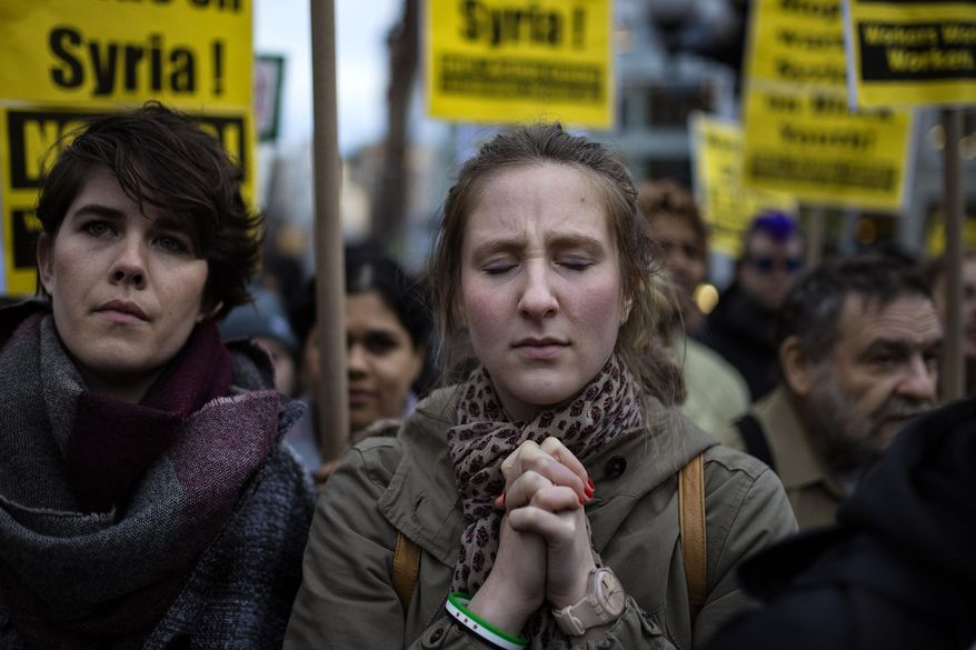 "A protester reacts during a rally against the U.S. missile strikes in Syria, Friday, April 7, 2017, in New York. Hundreds of demonstrators took to New York City streets chanting ""Hands off Syria!"" and ""Money for jobs and education, not for war and occupation!"" The U.S. fired a barrage of cruise missiles into Syria on Thursday night in retaliation for a chemical weapons attack against civilians earlier in the week. (AP Photo/Andres Kudacki)"