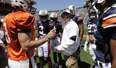 Auburn offensive coordinator Chip Lindsey, headphones, meets with his offense during a time-out in the first half of Auburn's NCAA college football spring game on Saturday, April 8, 2017 in Auburn, Ala. (AP Photo/Todd Van Emst)