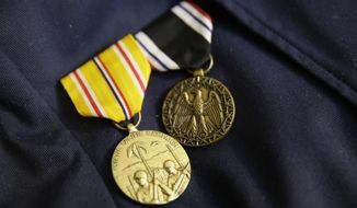 In this photo taken Thursday, April 6, 2017, a pair of medals are pinned to the jacket of Bataan Death March survivor Ramon Regalado at his home in El Cerrito, Calif. Survivors of the infamous Bataan Death March in the Philippines are marking the anniversary Saturday in San Francisco with speeches and a 21-gun battery salute to the thousands who died in it. Among the speakers will be Regalado, a former wartime machine-gun operator who turns 100 this month and is among the war's few living survivors. (AP Photo/Eric Risberg)