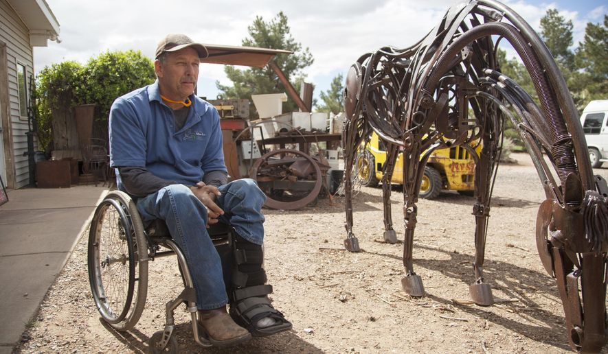 In this April 1, 2017 photo, local artist Matt Clark appears with one of his sculptures outside his workshop in St. George, Utah. Clark utilizes recycled, broken pieces of scrap metal in his art pieces. (Chris Caldwell/The Spectrum & Daily News via AP)