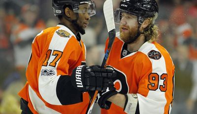 Philadelphia Flyers' Wayne Simmonds, left, congratulates Jakub Voracek after he scored a goal during the second period of an NHL hockey game against the Columbus Blue Jackets, Saturday, April 8, 2017, in Philadelphia. Simmonds was credited with an assist on the goal.(AP Photo/Tom Mihalek)