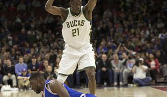 Milwaukee Bucks' Tony Snell, top, picks up the ball before Philadelphia 76ers' Alex Poythress, bottom, is able to get to it during the second half of an NBA basketball game, Saturday, April 8, 2017, in Philadelphia. (AP Photo/Chris Szagola)