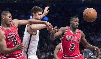 Chicago Bulls forward Cristiano Felicio (6) guard Jerian Grant (2) and Brooklyn Nets center Brook Lopez fight for a rebound during the first half of an NBA basketball game, Saturday, April 8, 2017, in New York. (AP Photo/Mary Altaffer)