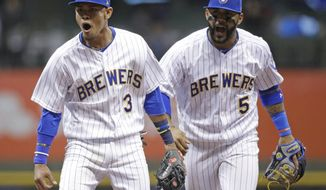 Milwaukee Brewers' Orlando Arcia (3) and Jonathan Villar react after turning a double play on a ball hit by Chicago Cubs' Ben Zobrist during the 10th inning of a baseball game Friday, April 7, 2017, in Milwaukee. (AP Photo/Jeffrey Phelps)