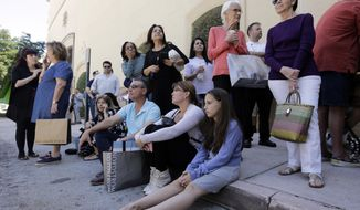 Shoppers Roman Lugo, seated, left, Siuris Rodriguez, center, and Chelsea Lugo, right, sit on the pavement after being evacuated from the Shops at Merrick Park after a shooting, Saturday, April 8, 2017, in Coral Gables, Fla.  Alvaro Zabaleta of the Miami-Dade Police Department says detectives have responded to the scene of the shooting in the upscale shopping mall in South Florida.  (AP Photo/Lynne Sladky)