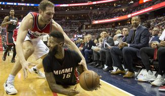 Miami Heat forward James Johnson (16) recovers a loose ball as he goes up against Washington Wizards guard Bojan Bogdanovic during the first half of an NBA basketball game in Washington, Saturday, April 8, 2017. Looking on is Miami Heat Assistant Coach Juwan Howard, right. (AP Photo/Pablo Martinez Monsivais)