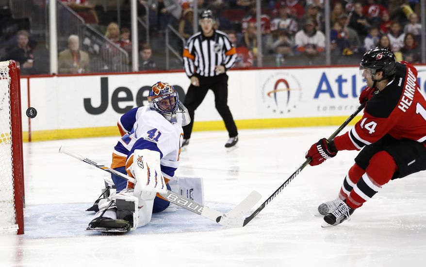 New York Islanders goalie Jaroslav Halak, left, of Slovakia, deflects a shot from New Jersey Devils center Adam Henrique during the second period of an NHL hockey game, Saturday, April 8, 2017, in Newark, N.J. (AP Photo/Julio Cortez)