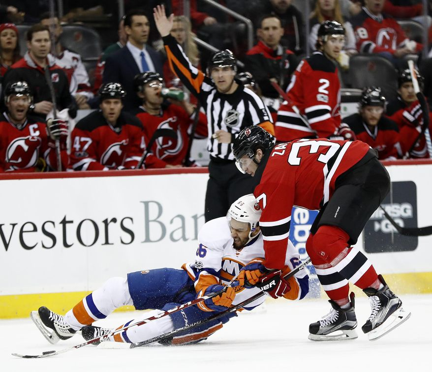 New York Islanders' Joshua Ho-Sang, left, and New Jersey Devils center Pavel Zacha, of the Czech Republic, compete for the puck during the first period of an NHL hockey game, Saturday, April 8, 2017, in Newark, N.J. (AP Photo/Julio Cortez)