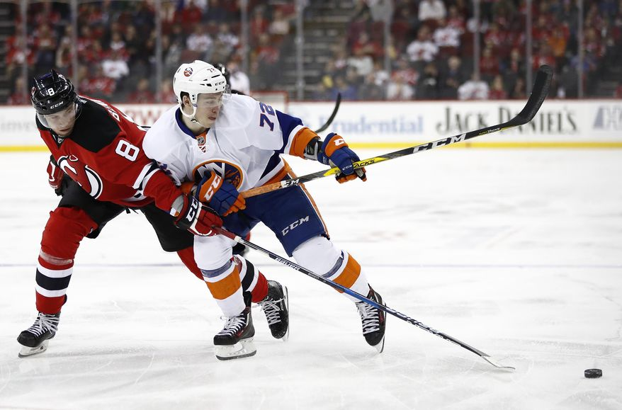 New Jersey Devils right wing Beau Bennett (8) and New York Islanders left wing Anthony Beauvillier (72) compete for the puck during the first period of an NHL hockey game, Saturday, April 8, 2017, in Newark, N.J. (AP Photo/Julio Cortez)