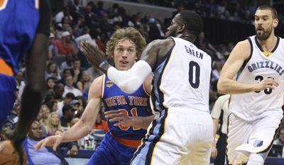 New York Knicks' Ron Baker drives on Memphis Grizzlies' JaMychal Green during the first half of an NBA basketball game Friday, April 7, 2017, in Memphis, Tenn. (AP Photo/Karen Pulfer Focht)