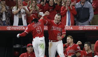 Los Angeles Angels' Cameron Maybin, left, celebrates his home run with Mike Trout during the sixth inning of a baseball game against the Seattle Mariners on Friday, April 7, 2017, in Anaheim, Calif. (AP Photo/Jae C. Hong)