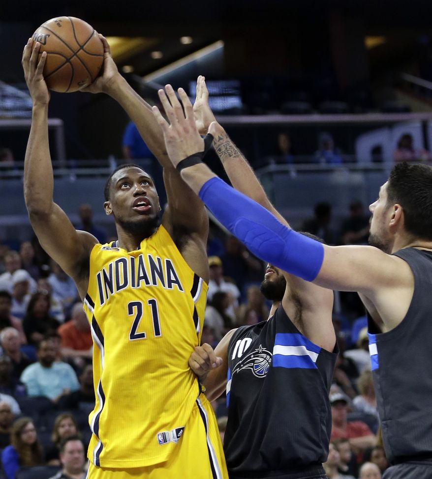 Indiana Pacers' Thaddeus Young (21) shoots over Orlando Magic's Evan Fournier, center, and Nikola Vucevic, right, during the first half of an NBA basketball game, Saturday, April 8, 2017, in Orlando, Fla. (AP Photo/John Raoux)