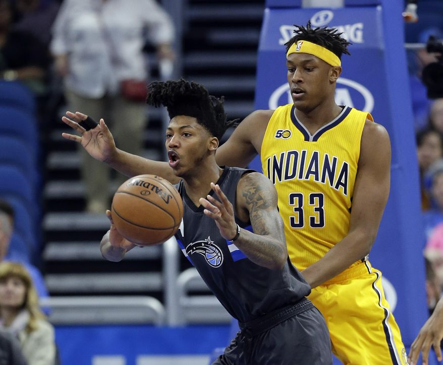 Orlando Magic's Elfrid Payton, left, passes the ball to a teammate as his path to the basket is blocked by Indiana Pacers' Myles Turner (33) during the first half of an NBA basketball game, Saturday, April 8, 2017, in Orlando, Fla. (AP Photo/John Raoux)