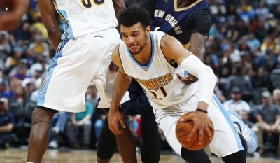 Denver Nuggets guard Jamal Murray, front, is fouled by New Orleans Pelicans guard Jrue Holiday, back right, as he tries to make his way past a pick set by Nuggets forward Kenneth Faried during the second half of an NBA basketball game Friday, April 7, 2017, in Denver. The Nuggets won 122-106. (AP Photo/David Zalubowski)