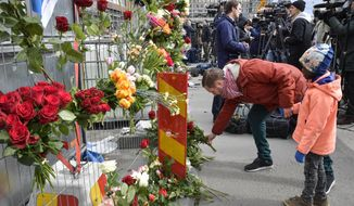 """Journalists work as people lay flowers near the scene following a suspected terror attack in central Stockholm, Sweden, Saturday, April 8, 2017.  A Swedish prosecutor Hans Ihrman said a person has been formally identified as a suspect """"of terrorist offences by murder"""" after a hijacked truck was driven into a crowd of pedestrians and crashed into a department store on Friday. (Anders Wiklund / TT via AP)"""