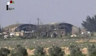 FILE - This file frame grab from video provided on Friday April, 7, 2017 by the Syrian official TV, a Syrian government channel that is consistent with independent AP reporting, shows the burned and damaged hangar warplanes which attacked by U.S. Tomahawk missiles, at the Shayrat Syrian government forces airbase, southeast of Homs, Syria. A U.S. missile attack on Friday, April 7, 2017 has caused heavy damage to one of Syria's biggest and most strategic air bases, used to launch warplanes to strike opposition-held areas in central, northern and southern Syria.  (Syrian government TV, via AP, File)