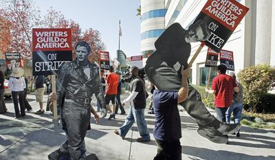 FILE - In this Nov. 26, 2007 file photo, striking writers carry live sized photos of legendary actors, Marlon Brando, left, and James Dean to express their support to members of the Writers Guild of America (WGA), outside the Raleigh Studios in Los Angeles. On Monday, April 10, 2017, the Writers Guild of America will pick up negotiations again with the Alliance of Motion Pictures and Television Producers, which represents broadcast networks and movie studios, over a new contract. The WGA is moving to authorize a strike, but Hollywood is hoping to avoid a work stoppage like the 100-day strike of 2007.  (AP Photo/Damian Dovarganes, File)