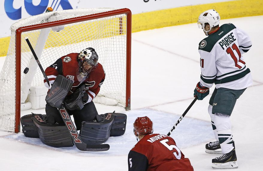Arizona Coyotes' Mike Smith, left, makes a save on a shot from Minnesota Wild's Zach Parise (11) as Coyotes' Connor Murphy (5) looks on during the first period of an NHL hockey game Saturday, April 8, 2017, in Glendale, Ariz. (AP Photo/Ross D. Franklin)