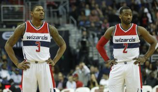 Washington Wizards Bradley Beal (3) and John Wall (2) wait for play to resume during the second half of an NBA basketball game against the Miami Heat in Washington, Saturday, April 8, 2017. Miami won 106-103. (AP Photo/Pablo Martinez Monsivais)