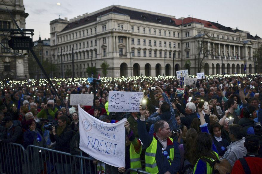 "Demonstrators in front of the parliament building in Budapest hold a banner reading ""Let's stop Fidesz"" (party) as they protest an amendment of the higher education law seen by many as an action aiming at the closure of the Central European University, founded by Hungarian born American billionaire businessman George Soros. (Associated Press/File)"