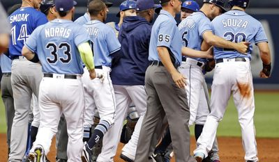 Tampa Bay Rays first base coach Rocco Baldelli, second from right, holds back Steven Souza Jr. as members of the Tampa Bay Rays and Toronto Blue Jays clear the benches following Souza Jr.'s slide into second base during the second inning of a baseball game, Sunday, April 9, 2017, in St. Petersburg, Fla. (AP Photo/Mike Carlson)