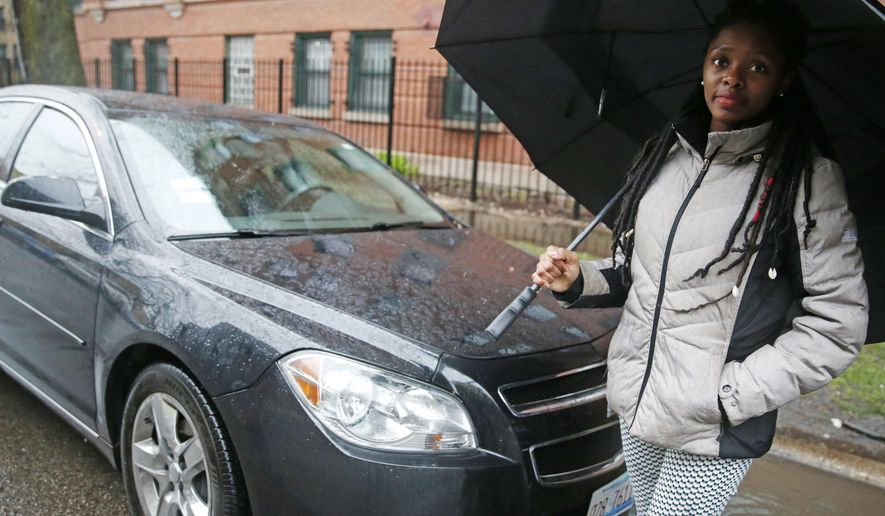 In this Wednesday, April 5, 2017 photo, Kara Bland stands in front of her car in Chicago. Bland's 2010 Chevy Malibu still had temporary plates when police seized it for a crime she did not commit. She loaned it to the father of her daughter, who was arrested after picking up someone who had marijuana on him. For six weeks, Bland took her daughter to school on a Chicago city bus and relatives helped her run errands before a judge released the car on bond. It took a total of nine months to officially regain ownership and cost her $1,000. (AP Photo/Nam Y. Huh)