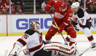 New Jersey Devils goalie Cory Schneider (35) stops a Detroit Red Wings left wing Matt Lorito (22) shot during the second period of the final NHL hockey game at Joe Louis Arena, Sunday, April 9, 2017, in Detroit. (AP Photo/Paul Sancya)